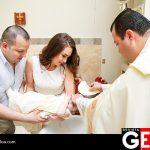 El bebé en brazos de sus padrinos al recibir el Bautizo